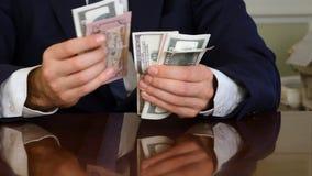 Un ` s dell'uomo d'affari passa il conteggio delle cento banconote in dollari ad una tavola fotografia stock libera da diritti