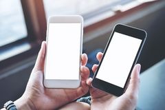 Un ` s della donna passa a tenuta due telefoni cellulari con lo schermo bianco in bianco in caffè moderno fotografia stock