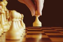 Un ` s della mano del giocatore di scacchi rende ad un movimento il pegno bianco di andata a immagine stock