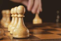 Un ` s della mano del giocatore di scacchi rende ad un movimento il pegno bianco di andata, ou Fotografie Stock Libere da Diritti