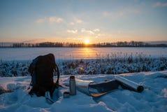 Un sac à dos, flacon de thermos et une couverture de voyage Beau coucher du soleil de l'hiver Style de vie actif Hausse en hiver images libres de droits