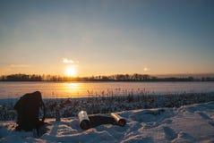 Un sac à dos, flacon de thermos et une couverture de voyage Beau coucher du soleil de l'hiver Style de vie actif Hausse en hiver photo libre de droits