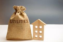 Un sac d'argent avec les utilités de mot et une maison en bois Le concept de l'argent économisant pour le paiement des utilités L photographie stock libre de droits