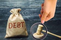 Un sac d'argent et de la dette de mot et le marteau du juge Paiement des imp?ts et de dette ? l'?tat Concept de financier photo libre de droits