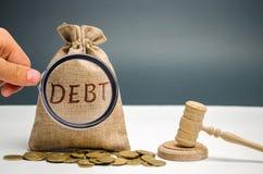 Un sac d'argent et de la dette de mot et le marteau du juge Paiement des imp?ts et de dette ? l'?tat Concept de financier image libre de droits