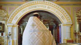 Un sacerdote anziano cristiano in abbigliamento festivo con i vetri prega stock footage