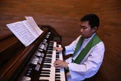 Un sacerdote católico que juega el órgano Imagenes de archivo