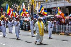 Un sacerdote del templo anda a trancos delante de un grupo de portadores de bandera budistas durante el día Perahera en Kandy en  Fotografía de archivo
