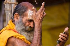 Un sacerdote hindú que aplica marcas de la frente en el Kumbha Mela en la India Fotos de archivo
