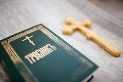 Un sacerdote lleva a cabo una cruz Imagen de archivo libre de regalías