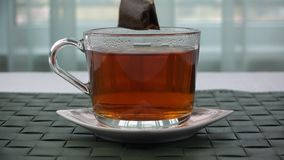 Un sachet à thé est pris d'une tasse de thé clips vidéos