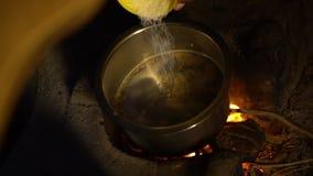 Un sale di versamento dell'indiano in un vaso del metallo su una fiamma aperta archivi video