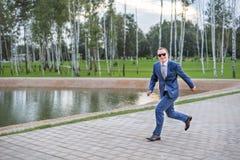 Un salto de funcionamiento del hombre de negocios joven en la calle imagenes de archivo