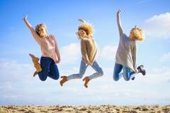 Un salto di tre donne fotografia stock