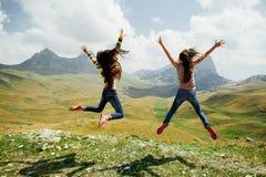 Un salto felice di due ragazze in montagne con la vista emozionante Fotografia Stock Libera da Diritti