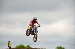 Un salto sopra il corridore di motocross della collina Fotografia Stock