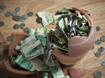 Un salvadanaio rotto con le banconote saudite del riyal e le monete 4 Fotografia Stock