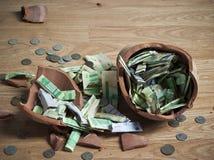 Un salvadanaio rotto con le banconote saudite del riyal e le monete 2 Fotografie Stock