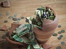 Un salvadanaio rotto con le banconote saudite del riyal e le monete 3 Fotografie Stock Libere da Diritti