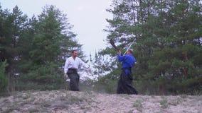 Un samouraï dans un kimono bleu se défend contre un samouraï avec un halberdo, le repousse avec un coup-de-pied de son pied clips vidéos