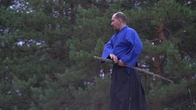 Un samurai calvo confiado adentro con un kimono azul camina a través del bosque y se convierte en la posición que lucha que  almacen de video