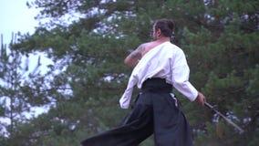 Un samurai con un tatuaje desenrolla maravillosamente una alabarda pesada para pegar encima de un samurai con un katana, cámara l metrajes