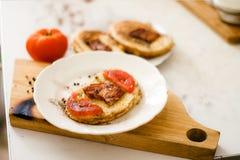Un sandwich chaud frit frais lumineux et délicieux avec des tranches d'oeufs, de lard et de tomate sur le pain Image stock