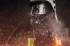 Un sapeur-pompier s'est habillé dans un uniforme dans un studio photographie stock