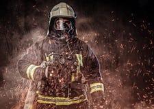 Un sapeur-pompier s'est habillé dans un uniforme dans un studio photo stock