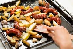 Un sartén grande con las comidas grasas: salchichas, patatas de una manera rústica Mano y espátula de madera fotos de archivo libres de regalías