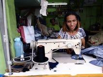 Un sarto lavora ad un interno del vestito un negozio d'adattamento immagini stock