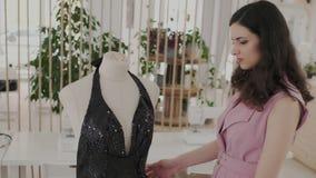 Un sastre bonito camina alrededor de un maniquí con un vestido de noche de moda Vestido brillante oscuro con una tela profunda de metrajes