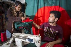 Un sastre joven Md Rashed Alam, envejece 28 banderas nacionales de Bangladesh de fabricación en Dacca, Bangladesh imagenes de archivo