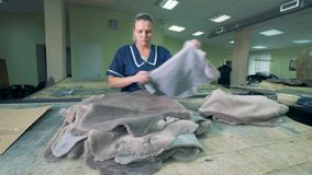 Un sastre que trabaja con las pieles animales en una fábrica, cierre para arriba almacen de metraje de vídeo