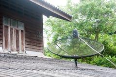 Un satellite sur le toit de la maison très vieille de cru avec le fond d'arbre photos stock