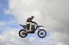Un saut au-dessus du coureur de motocross de côte Photographie stock libre de droits