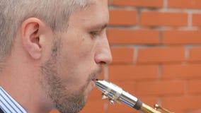 Un saxofonista toca el saxofón almacen de video