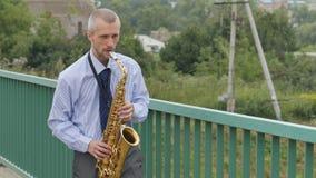 Un saxofonista toca el saxofón metrajes
