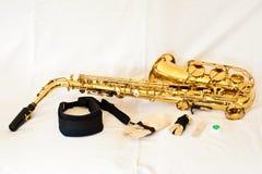 Un or/saxophone en laiton d'alto sur le fond blanc avec des clés de perle - présentées avec des accessoires photographie stock libre de droits