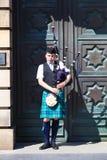 Un Scotsman que lleva el equipo escocés tradicional que toca las gaitas Fotos de archivo