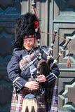 Un Scotsman que lleva el equipo escocés tradicional que toca las gaitas Foto de archivo libre de regalías