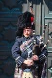 Un Scotsman que lleva el equipo escocés tradicional que toca las gaitas Fotografía de archivo