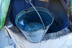 Un seau de l'eau au bord d'un puits Image stock