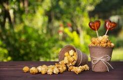 Un seau de papier avec le maïs éclaté et les lucettes caramélisés sur un fond naturel vert Un seau avec le maïs éclaté dispersé Photographie stock libre de droits
