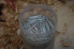 Un secchio dei chiodi sul banco di falegnameria immagine stock