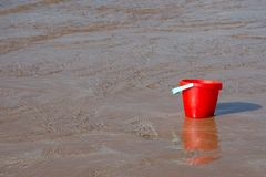 Un secchio rosso assorbe la marea che entra in spiaggia fotografia stock libera da diritti