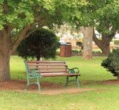 Un sedile del parco sotto un albero un giorno soleggiato immagini stock libere da diritti