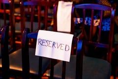 Un sedile di legno del teatro con il segno riservato scritto a mano fotografia stock