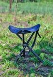 Un seggiolone piegante blu per il campeggio su una radura di verde di estate Fotografie Stock Libere da Diritti