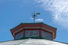 Un segnavento in cima ad una vecchia costruzione, contro un cielo blu con alcune nuvole lanuginose leggere fotografie stock